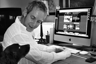 Photo of Steve Hall at work with dog looking on.